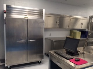 Received new equipment such as Hobart mixer, wall mounted pot rack, and cabinets above sink, reach-in cooler, food warmer, serving line with cashier's table.