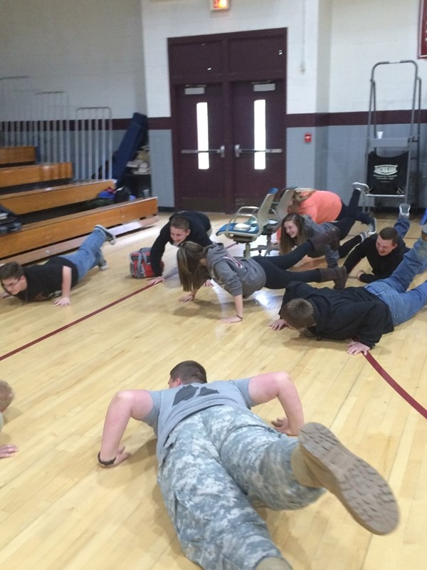 JCHS ROTC doing push-ups with the students JCMS Career Day