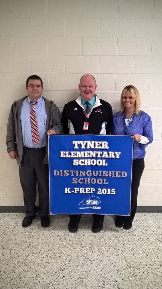 Tyner Elementary exceeded it's 2015 AMO Goal on state assessment, was classified as a Distinguished School and also earned the status of High Performing School/High Progress School.  Mr. Smith, Mr. Johnson, and Mrs. Bingham with school banner.